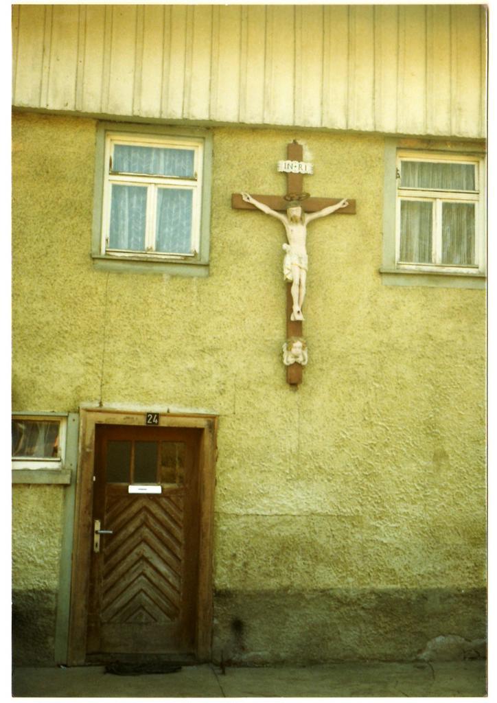 Kreuz an Brunnenmachers Haus. Nachdem das alte Brunnenmacherhaus nicht mehr existiert, ist das Kreuz renoviert worden und hängt jetzt im Dunninger Rathaus, wo ein kleines Täfelchen auf seine Herkunft hinweist. Man nimmt an, dass das Kreuz aus dem 17. Jahrhundert stammt. [Seite 27]